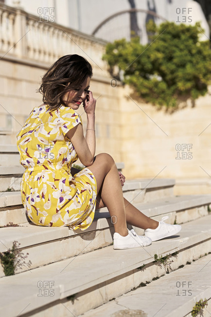 Full body side view of dreamy young slender female in short yellow summer dress looking down with hand at cheek while chilling on staircase in sunlight