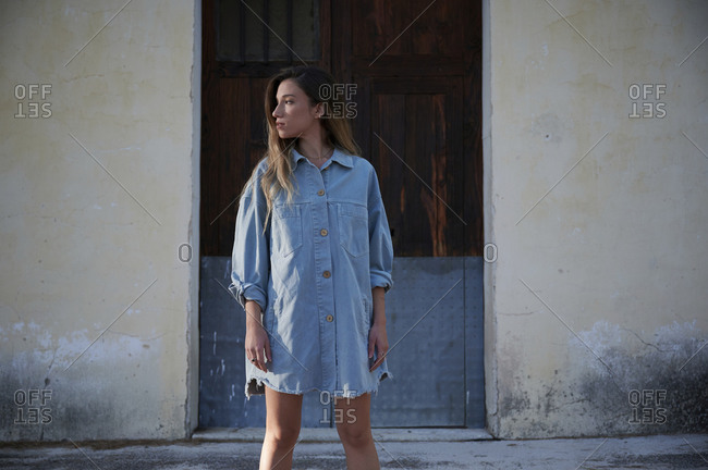 Young slim female in stylish denim dress and boots standing on grassy lawn covered with hoarfrost against weathered rural house in autumn day