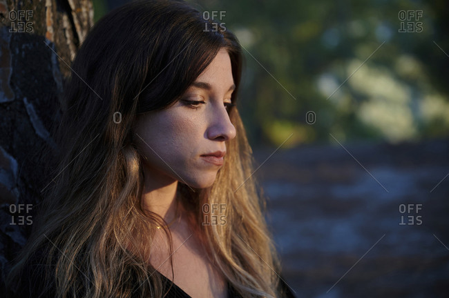 Side view of silent sad young long haired female leaning back on tree trunk while standing against blurred forest