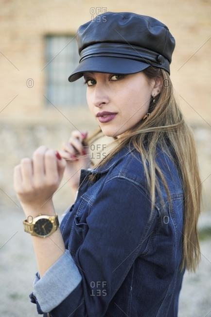 Side view of confident female wearing denim jacket and trendy leather cap standing on street and looking at camera