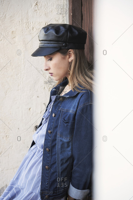 Side view of thoughtful young female wearing trendy leather cap and summer clothes leaning on wooden door of building in city and looking down