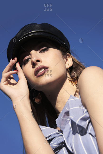 From below of stylish female model wearing fashionable leather cap and summer dress looking at camera on background of blue sky