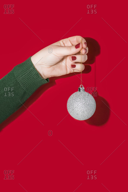 Crop hand of female holding shiny silver Christmas ball against bright red background