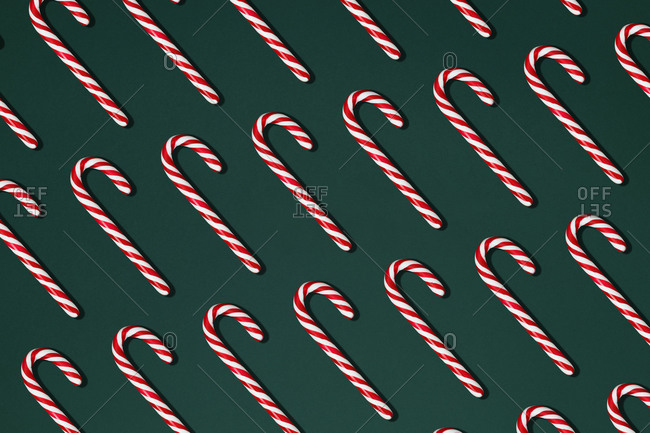 Top view composition with red Christmas candy canes arranged in rows on black background