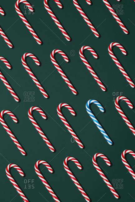 Top view composition with blue and red Christmas candy canes arranged in rows on black background