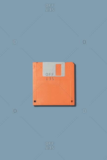 Top view of old fashioned orange magnetic floppy disk for computer placed on gray background