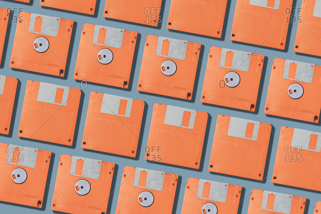 Top view layout with set of vintage orange computer floppy disks arranged in rows on gray background