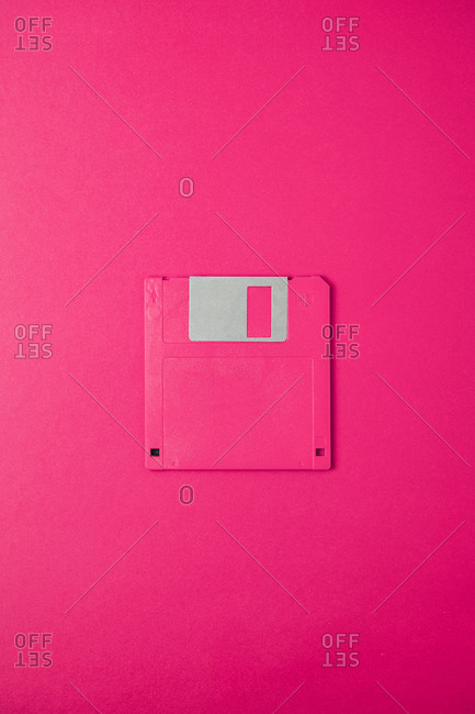 Top view of old fashioned pink magnetic floppy disk for computer placed on pink background