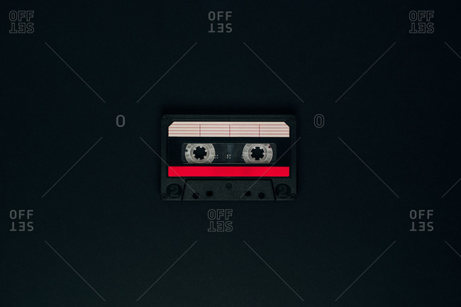 Top view of vintage compact audio tape with paper sticker placed on black background