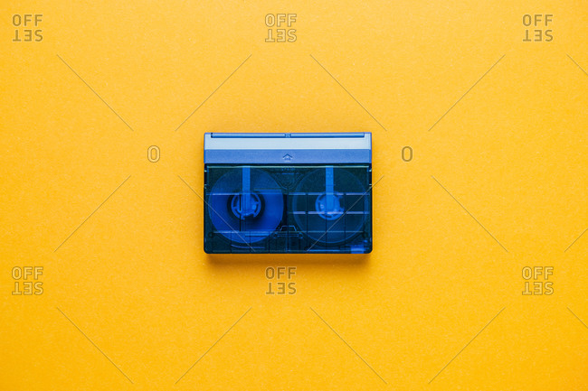 Top view of obsolete transparent audio tape cassette placed on bright yellow background