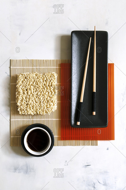 From above of round Asian noodles and wooden chopsticks arranged on bamboo mat on table in cafe