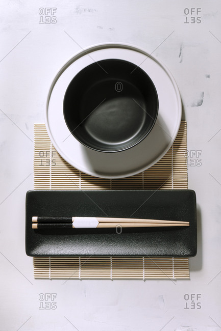 Top view of empty bowl placed on bamboo mat near wooden chopsticks on table