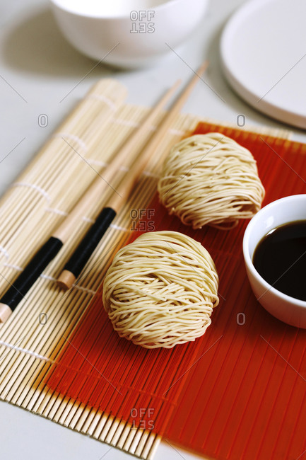 High angle of arrangement of round shaped dry noodles and soy sauce on table with wooden chopsticks
