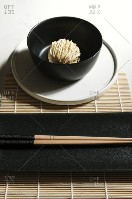From above of dry noodles in bowl arranged on bamboo mat with wooden chopsticks