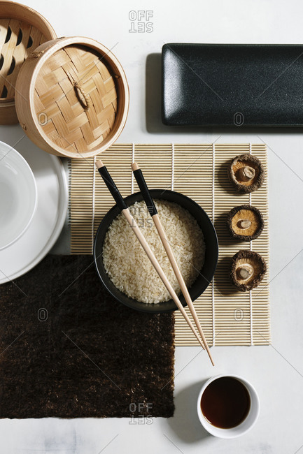 Top view of rice in bowl with wooden chopsticks arranged on table with soy sauce and dry noodles
