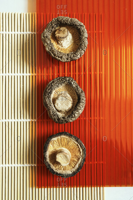Top view of appetizing dry shiitake mushrooms arranged in row on bamboo mat on table