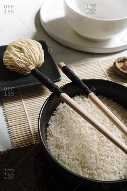 From above of rice in bowl with wooden chopsticks arranged on table with soy sauce and dry noodles