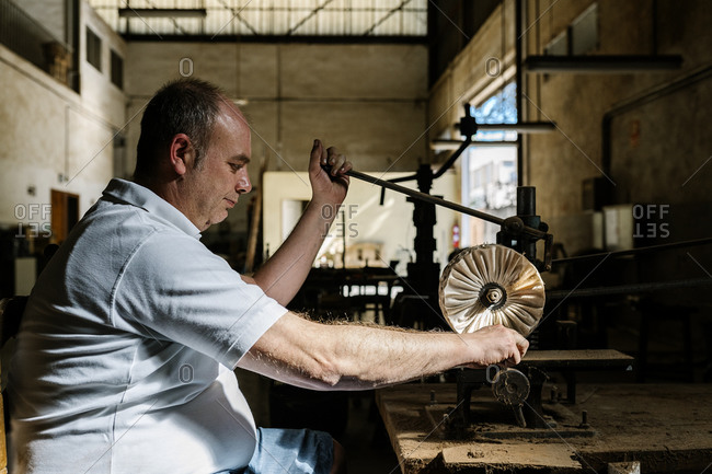 Side view of content craftsman sitting at wooden workbench in messy workshop and producing folding fans while using old machine