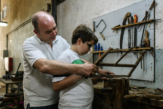 Side view of father teaching son using metal rasp for grinding wood in grungy dirty woodwork workshop