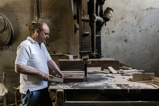 Talented male woodworker using band saw for cutting wooden plank in grungy workshop