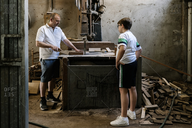 Curious teenage boy watching father standing at workbench and cutting wooden plank with band saw in grungy workshop