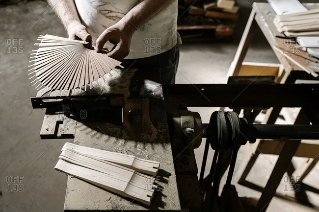 From above of unrecognizable crop craftsman working in dirty workshop at dusty workbench while standing with wooden folding fan