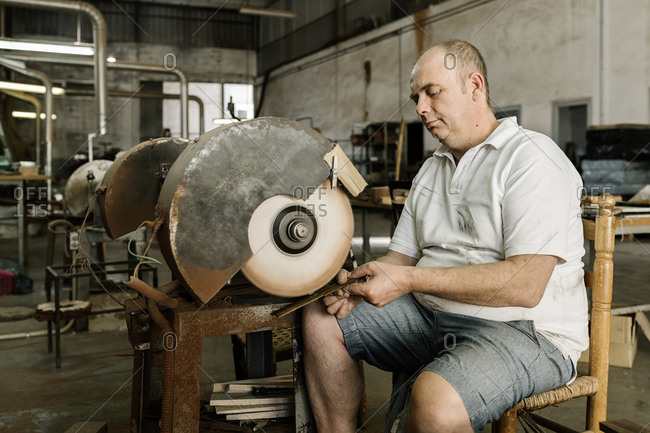Craftsman using grinding machine while making creative wooden folding fan in shabby workshop