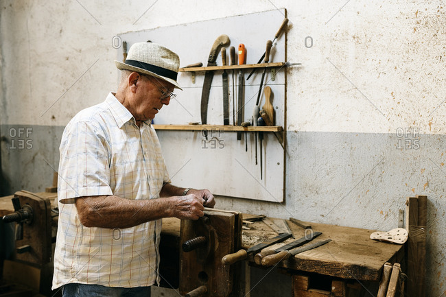 Side view of senior male carpenter grinding wooden details while making handmade folding fans in messy workshop