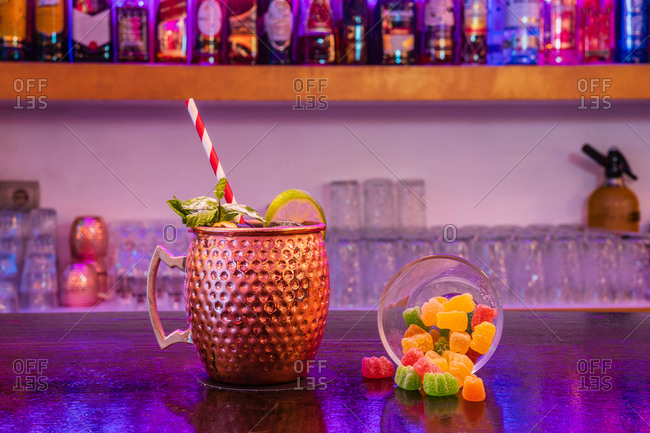 Moscow mule cocktail with straw served with lime and mint leaves on counter near glass of marmalade sweets