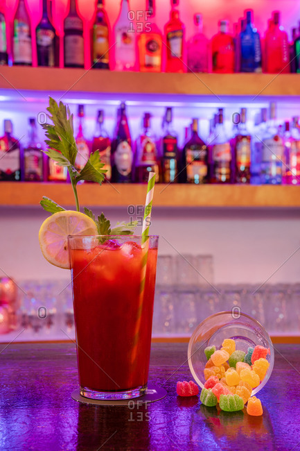 Crystal glass with Bloody Mary cocktail containing vodka tomato juice served with sweets on counter in bar