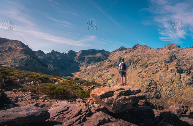 Back view of unrecognizable male traveler contemplating mountains under bright sky in twilight in Spain