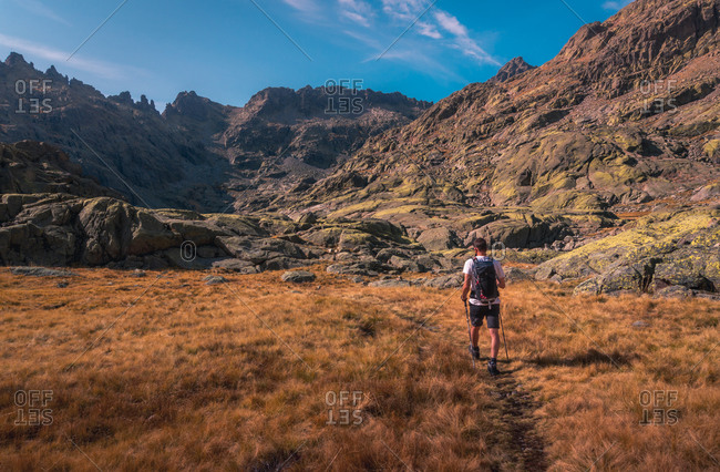 From above back view of unrecognizable male tourist with rucksack trekking with poles on rough pathway in mountains under sky