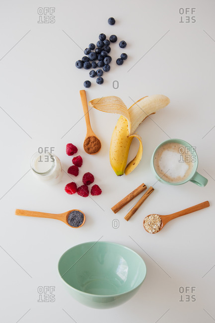 From above composition with fresh berries and banana with seeds and bottle of milk for healthy breakfast meal arranged with empty bowl on white table