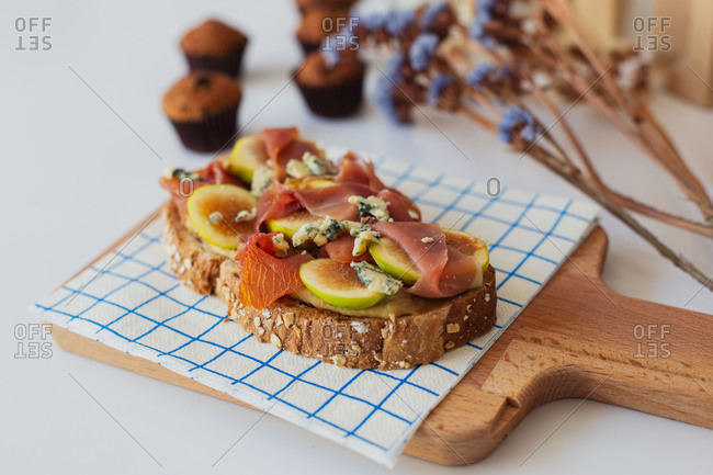 Appetizing homemade sandwich made with wholegrain bread toast and fresh sliced fruit with ham served for breakfast on wooden board