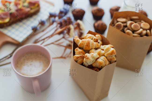 From above of paper bag with yummy sweet mini croissants placed on table with assorted pastry and mug of hot aromatic coffee