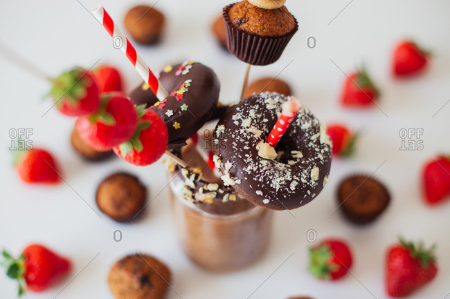 Glass of chocolate milkshake garnished with fresh strawberries and assorted sweet pastry on white table
