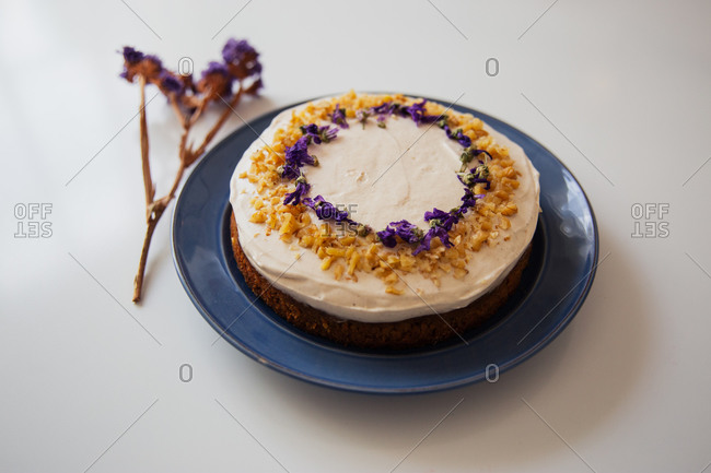 Appetizing rustic homemade cake topped with white cream and decorated with nuts and edible flowers served on plate on white table