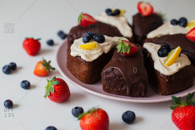 Closeup delectable homemade chocolate cake with white and chocolate cream decorated with fresh berries and lemon slices and cut into pieces