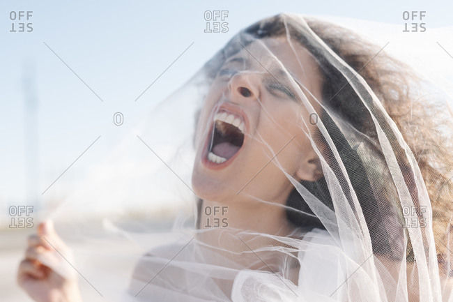 Young angry female with curly hair screaming through transparent veil on sunny clear day