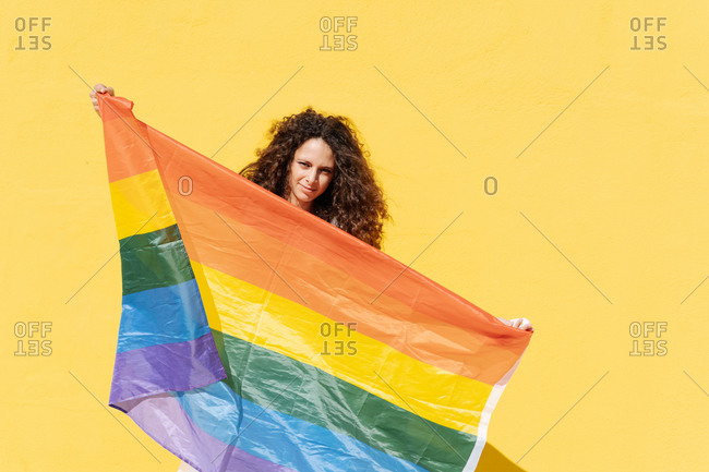 Young female with curly hair squinting and carrying LGBT flag on vivid yellow background