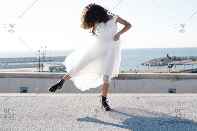 Rebellious unrecognizable female in elegant white dress and brutal boots dancing on rooftop in sunlight
