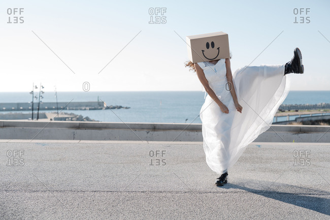 Unrecognizable woman wearing white bridal dresses and carton boxes with happy smileys dancing on sunny concrete pathway
