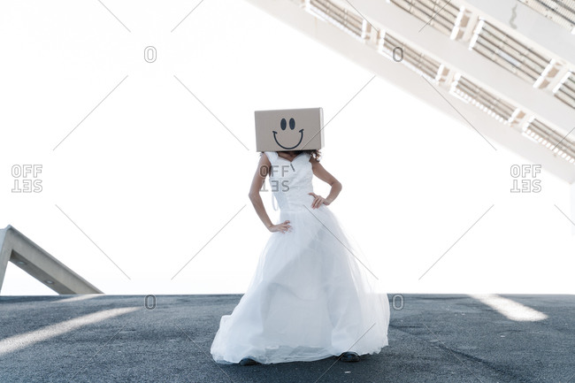 Full body of anonymous female in bridal dress with smiling box on head in bridal dress holding hands on waist under roof of local building