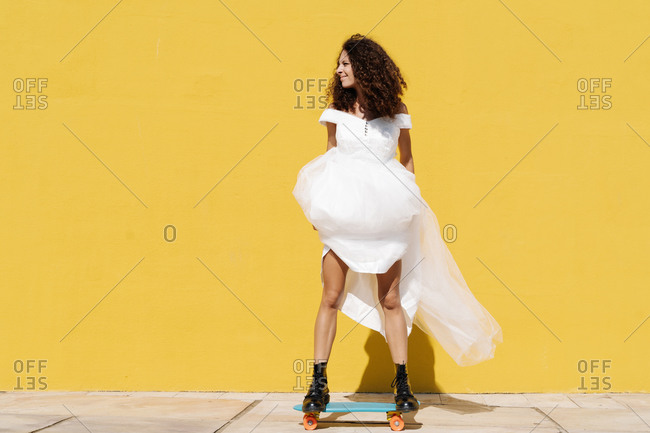 Full body of happy cheerful bride in white dress and boots standing on longboard against yellow background in sunlight