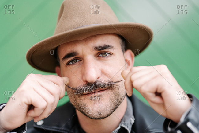 Mature male in leather jacket curling mustache while looking at camera standing on green gate