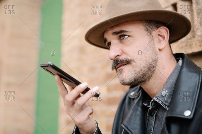 Side view of bearded male with mustache in hat and leather jacket using mobile phone and sending voice message on blurred background of building looking away