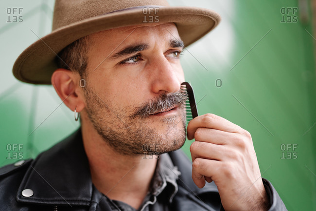 Stylish thoughtful male with earring wearing hat and leather jacket and brushing gorgeous mustache looking away