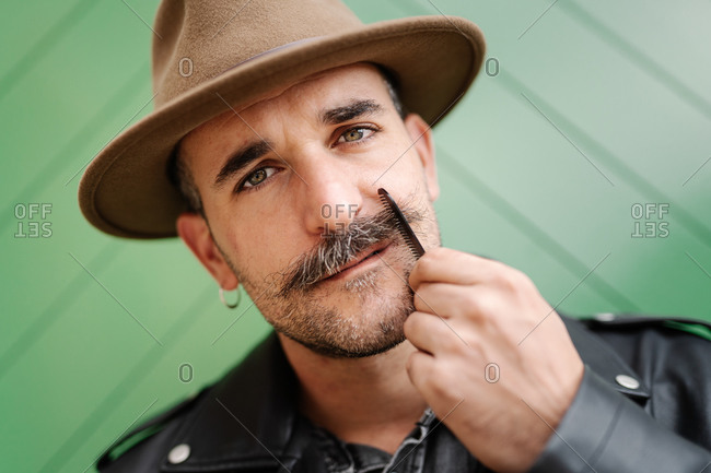 Stylish thoughtful male with earring wearing hat and leather jacket and brushing gorgeous mustache looking at camera