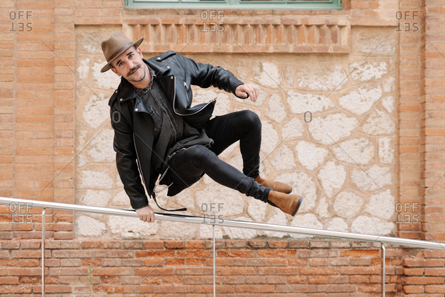 Full body of cheerful male with mustache wearing hat with leather jacket and jeans touching steel railing and looking at camera