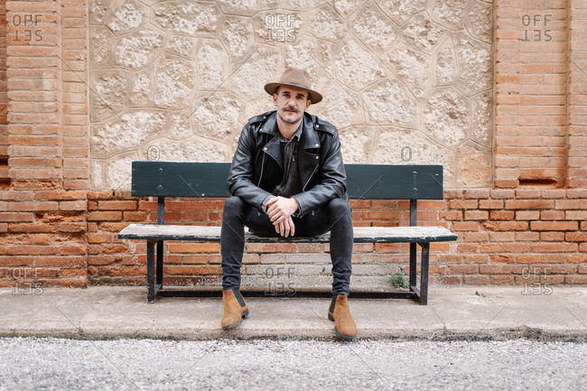 Serious male with mustache wearing hat and leather jacket relaxing on bench and looking at camera near stone brick wall